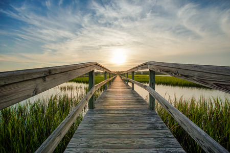 sunset over coastal waters with a very long wooden boardwalk Stock fotó