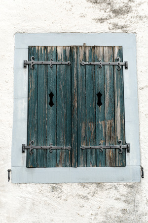 rustic faded vintage wooden window shutter set in a stone wall Stock Photo