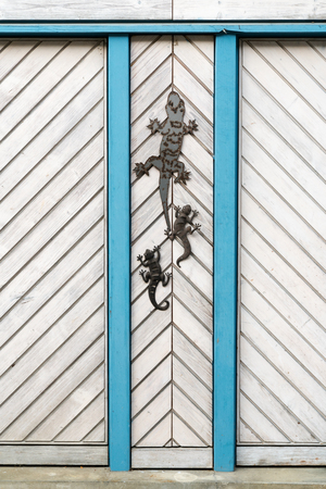 close up view of a white wooden door with blue siding and metal lizards as decoration