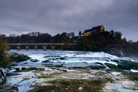 vertical landscape view of the famous Rhine Falls in Switzerland in the evening during twilight with a blurred train crossing the bridge