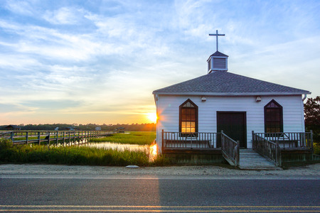 small white wooden chapel on the water on the coast during a colorful summer sunset with illuminated golden windows and a setting sun under a blue sky with soft clouds Stock Photo