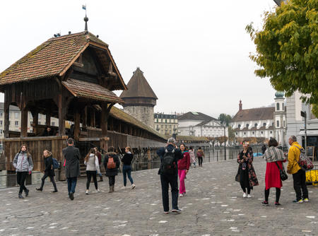 Lucerne, LU / Switzerland - November 9, 2018: tourists visit the famous Swiss city of Lucerne and take pictures of themselves with the Chapel Bridge  behind them as they stand on the river banks of the Reuss