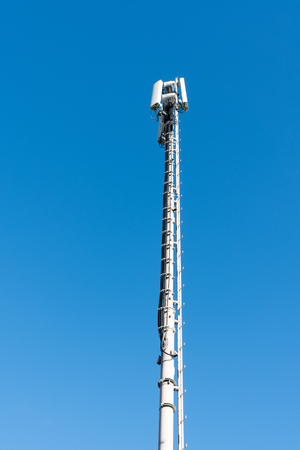 vertical view of a tall antenna tower for mobile and cellular telephone service with a blue sky background