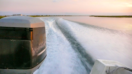 wake and waves and close up of an outboard engine in coastal waters at sunset with marsh grass in the background Stock Photo