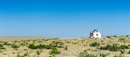 old dilapidated and abandoned white wooden house on the remote prairie in the middlew of nowhere under a blue sky