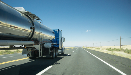truck with a silver tank trailer passing a passenger car on a highway Stockfoto