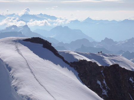 high alpine mountain peak with four climbers heading to the top and  a great view