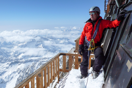 ski mountain climber on the balcony of the mountain hut on top of Signalkuppe with a great view of the Alps around Zermatt in the Monte Rosa range in Switzerland