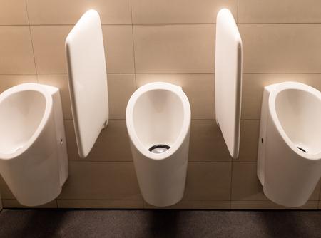 clean white modern ceramic urinals in a modern public toilet for men Stock Photo