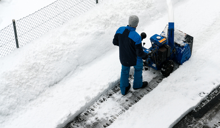 man with a snow blower clears snow from a road after a heavy snowfall in the Swiss Alps in winter