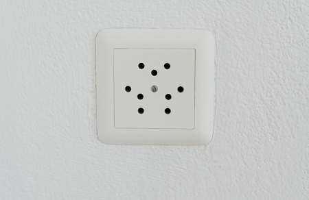 electrical socket for a Swiss plug close up view on a white wall