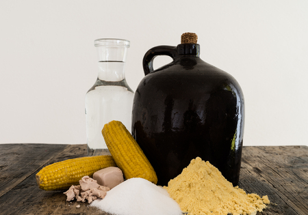 A clay half gallon jug with cob and the ingredients for making moonshine corn liquor on a rustic wooden table