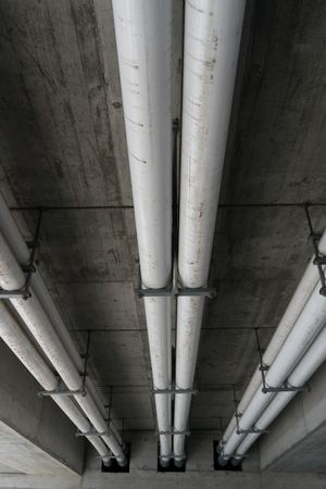 white industrial sewage and water pipes underneath a concrete bridge in Switzerland