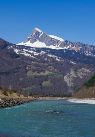 Rhine river in the springtime with snow-capped mountain peak landscape of Switzerland in the bakcground