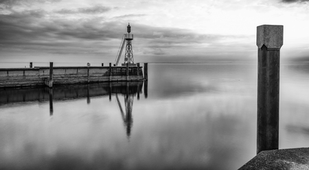 The harbor jetty at Rorschach harbor on a typical April spring morning on Lake Constance in Switzerland. Long exposure with lots of negative space. Stock Photo