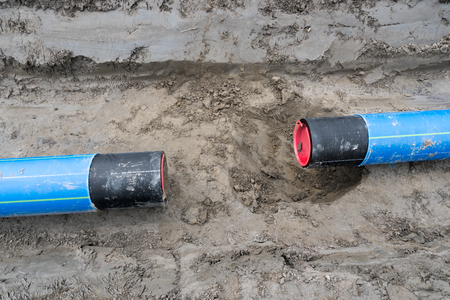 laying large industrial water pipes in an earth and dirt ditch for water supply and irrigation in the Swiss countryside Stock Photo