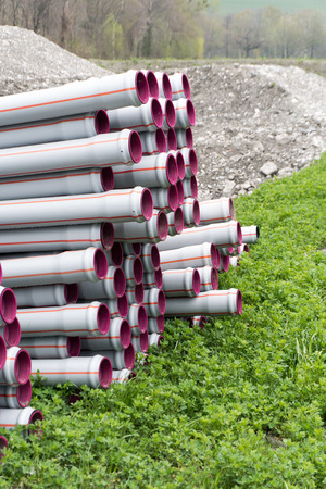many stacked long plastic pipe tubes ready for building a water supply and irrigation system on agricultural grounds