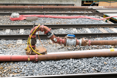 pipe and valve system with sensors and electrical wiring between railroad tracks as a temporary supply system during construction and renovation Stock Photo