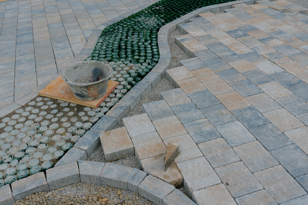 landscape gardening construction site of a natural stone courtyard with an innovative glass bottle walkway