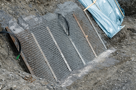 A view of slab concrete and rebar iron for slope reinforcement at an excavation and building site 스톡 콘텐츠