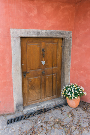 low and small cellar door with a heart-shaped ornament and flower pot in an old red house front in Europe