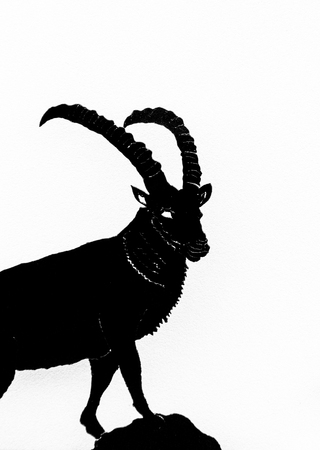 A vertical black and white illustration of a mountain goat ibex in silhouette on a white background