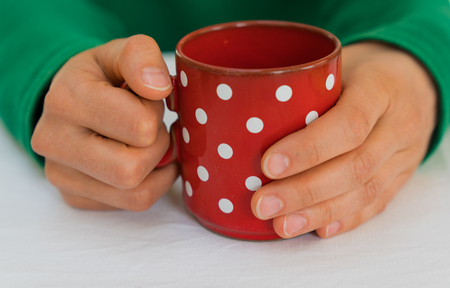 delicate female hands of a woman in a bright green sweater holding an empty red coffee cup with white polka dots on a white tablecloth