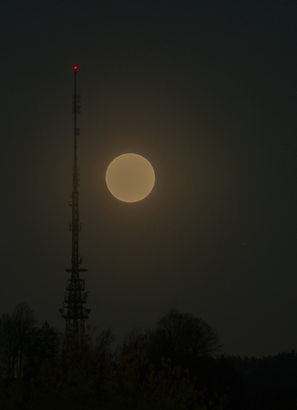 A full moon rising into the night sky with a radio antenna and transmission tower with a red signal light