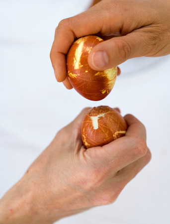 male and female hand tapping naturally colored eggs during Easter over a white background