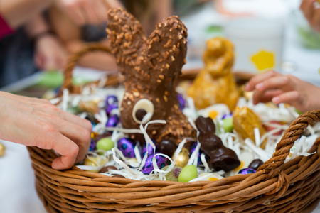 many hands reach for sweets candy and chocolate in an Easter egg basket during Easter celebrations with family and relatives