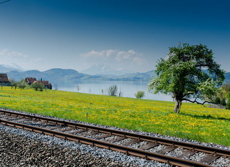 railroad tracks running along the side of the Zugersee lake in the central Swiss Alps