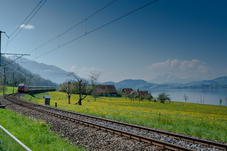 a train speeding along the railroad tracks running along the side of the Zugersee lake in the central Swiss Alps