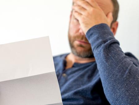 un uomo sulla quarantina seduto su un divano raggiunge emotivamente le cattive notizie che riceve in una lettera con messa a fuoco selettiva e spazio di copia Archivio Fotografico
