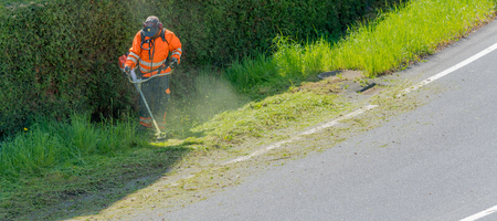 a city worker clearing the roadside of grass and weeds with a weed eater
