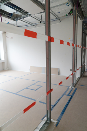 long hallway on a construction site cordoned off with red and white security tape to prevent damage Stock Photo