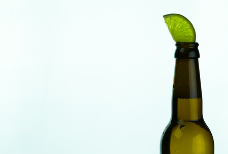 isolated brown beer bottle with a slice of green lime on a white background and copy space 写真素材