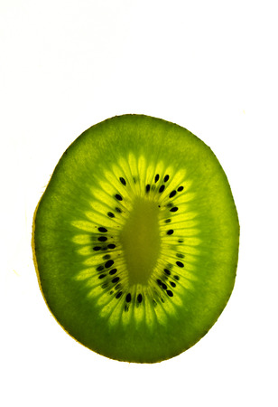 close up view of an isolated and backlit green kiwi fruit slice on a bright white background with copy space