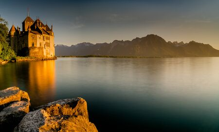 Montreux, VD / Switzerland - 31 May 2019: the historic Chillon Castle on the shores of Lake Geneva at sunset