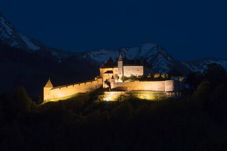 Gruyere, VD / Switzerland - 31 May 2019: view the historic castle at Gruyere with snowcapped mountain landscape at twilight