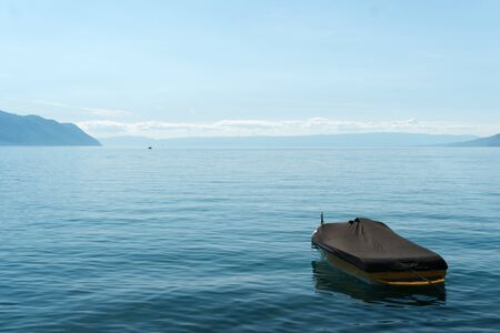 A beautiful view of Lake Geneva and surrounding mountains on a summer day with a single boat in the foreground Standard-Bild