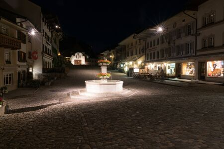 Gruyeres, VD / Switzerland - 31 May 2019: the historic medieval village of Gruyeres with the village square fountain at night