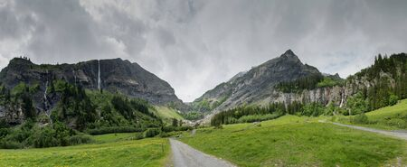 panorama mountain landscape with lush green forest and several waterfalls in the Swiss Alps on an overcast summer day