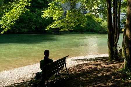 Horizontal view of a woman sitting on a bench under shady trees on an idyllic river bank