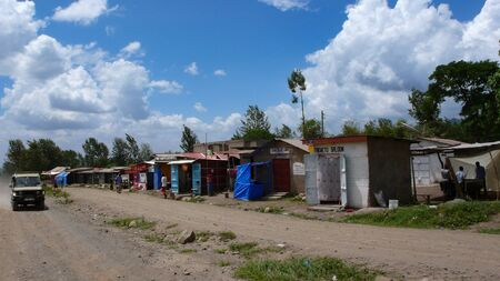 Moshi, Kilimanjaro Province / Tanzania: 2. January 2016: ramshackle village made of recycled materials on the roadside in Tanzania with shops and small homes for local people