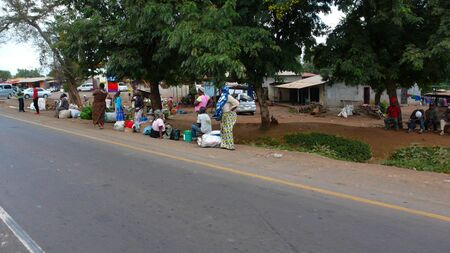 Moshi, Kilimanjaro Province / Tanzania: 2. January 2016: local people wait at the bus stop and chat after coming from the daily market in the town center of Moshi Editorial