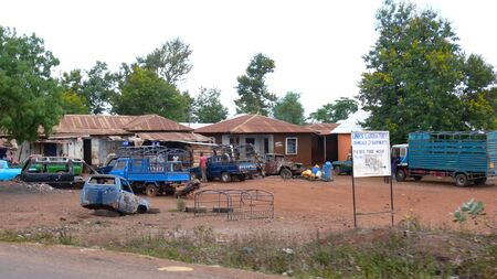 Moshi, Kilimanjaro Province / Tanzania: 2. January, 2016: garage and equipment supply store in rural Tanzania with damaged and old vehicles in the courtyard