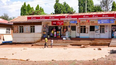 Moshi, Kilimanjaro Province / Tanzania: 2. January, 2016: country store with young kids walking by in front in rural Tanzania near Moshi