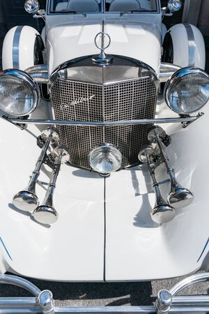 Bad Ragaz, SG / Switzerland - 23 June, 2019: radiator and headlights of a classic white Excalibur convertible sports car at the Heidiland Classic Car Meet