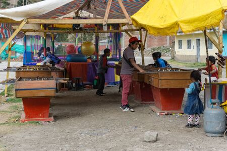Chavin de Huantar, Ancash / Peru - 11. June, 2016: young people and children enjoy a game of table football and more at a makeshift arcade