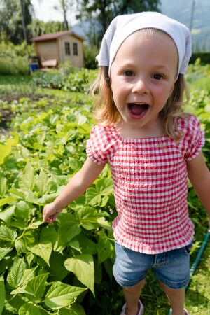 excited young girl points to the fast growing beans in her vegetable patch and smiles Stock Photo